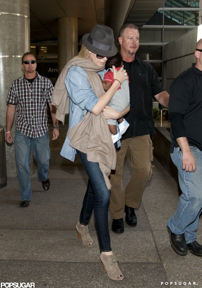 Charlize Theron wore a scarf and fedora when arriving at LAX.