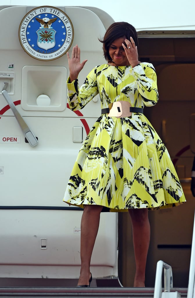 The FLOTUS selected a chartreuse printed Kenzo look since founding designer Kenzo Takada hails from Japan. Because the label is now run by Humberto Leon and Carol Lim in America, Michelle's dress selection connects both countries. The FLOTUS completed her look by cinching her waist with a Roksanda Ilincic belt and accessorizing with black pumps and her engagement ring.