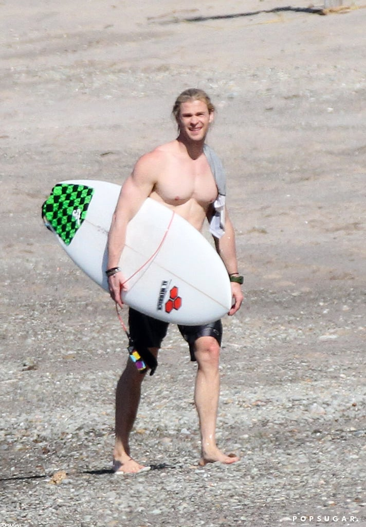 Shirtless Chris Hemsworth carried his surf board.