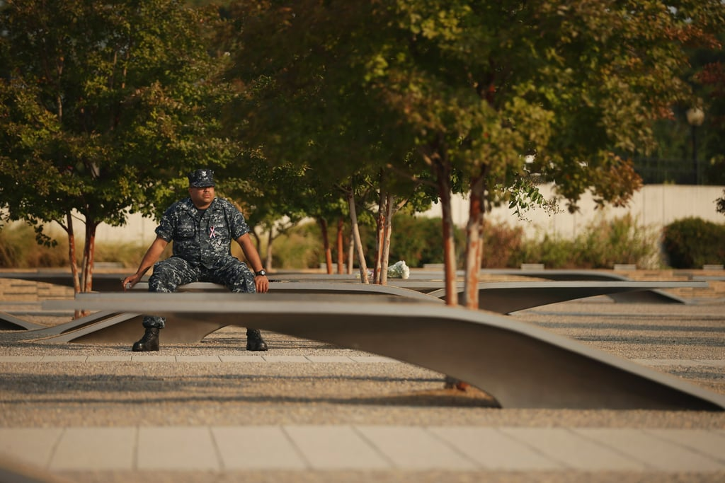 A man sat beside the memorial site before an observance ceremony at the Pentagon in Arlington, VA.