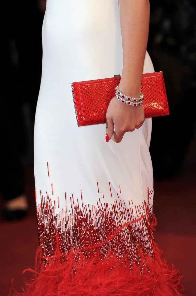 Cheryl accessorized her stunning Stéphane Rolland Couture gown with a exotic skin red clutch and a set of jewel-encrusted bracelets.