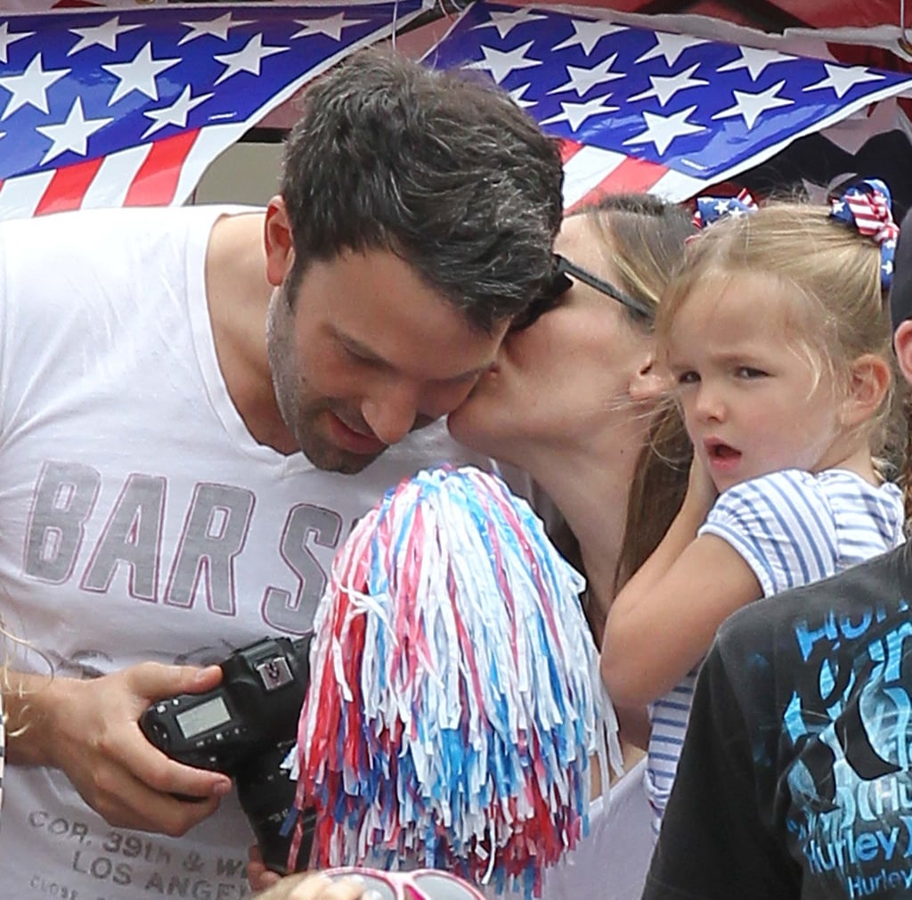 Jennifer Garner gave Ben Affleck a kiss on the cheek during a Fourth of July parade in LA while holding Seraphina Affleck in July 2012.