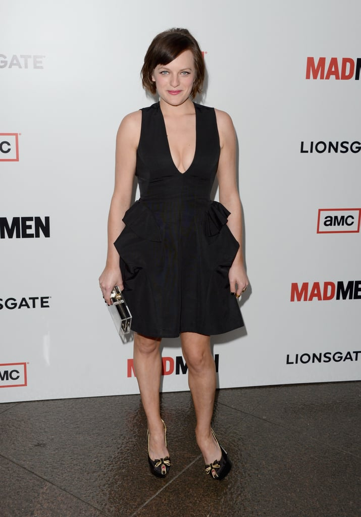 Elisabeth Moss stuck to the classics in a peplum-trimmed black cocktail dress by McQ Alexander McQueen, Lucite Charlotte Olympia clutch, and bow-adorned heels.
