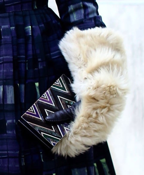 A furry mitten clutches on a statement printed minaudière.