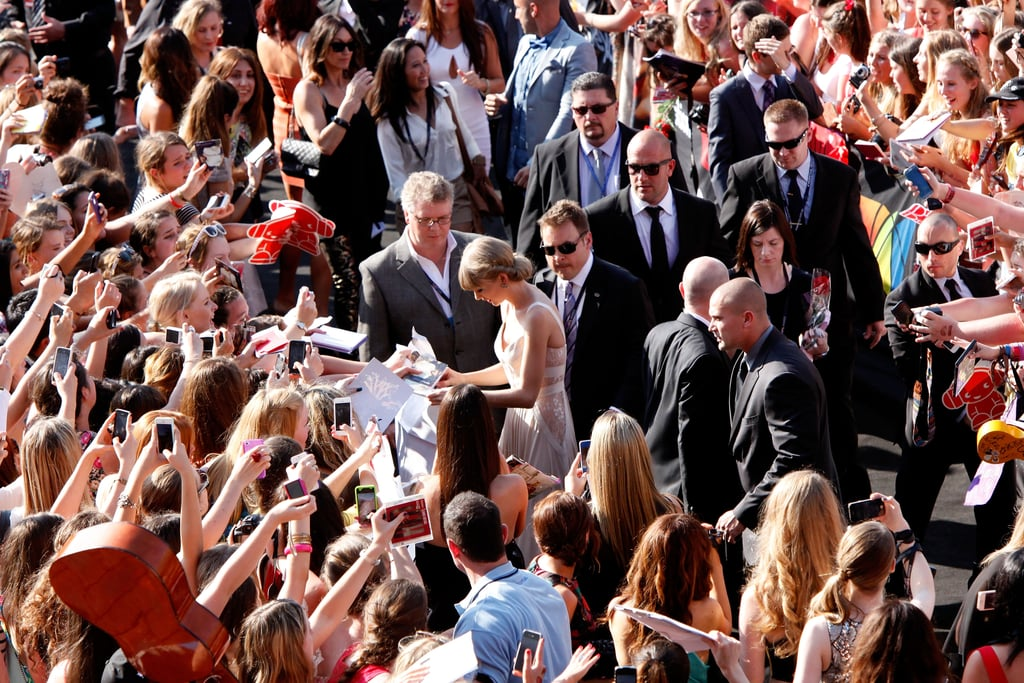 Look at all the security who escorted Taylor Swift down the ARIAs black carpet! She skipped the media line but had plenty of time for fans who had waited in the hot sun to see her.