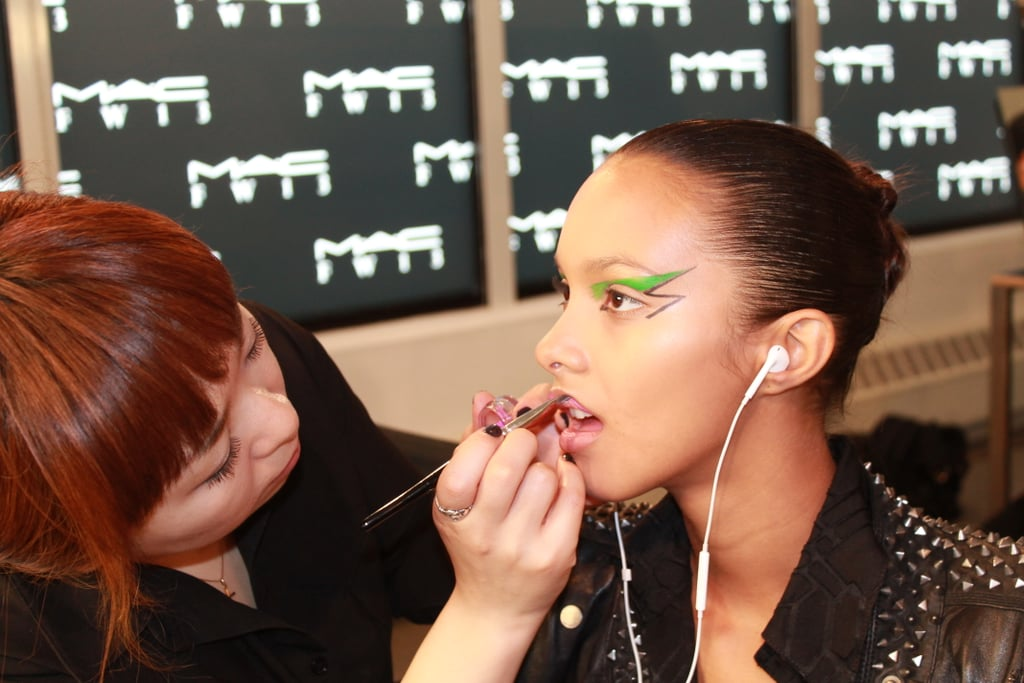 After prepping the skin with a touch of foundation, concealer, and loose powder, Kabuki painted MAC Up the Amp Lipstick onto the models' pouts.