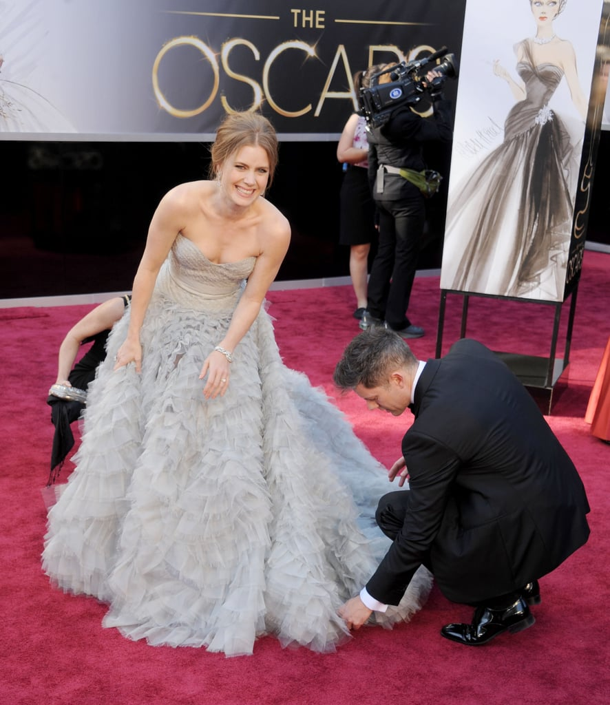 Too cute! Darren squatted down to help fix Amy's dress at the 2013 Oscars, where Amy was nominated for best supporting actress for her role in The Master.