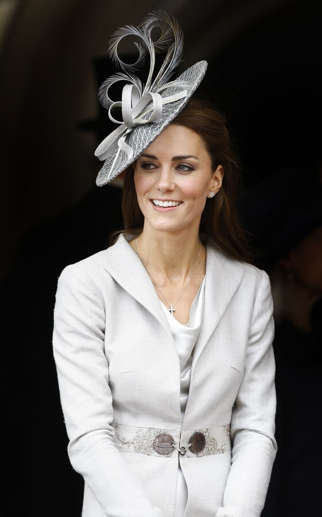 She matched a slick, long gray coat with a fanciful gray fascinator in June 2011.