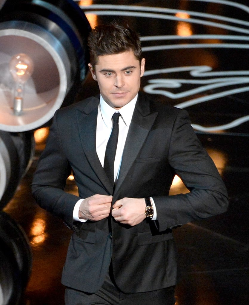 Zac Efron buttoned his jacket on stage.