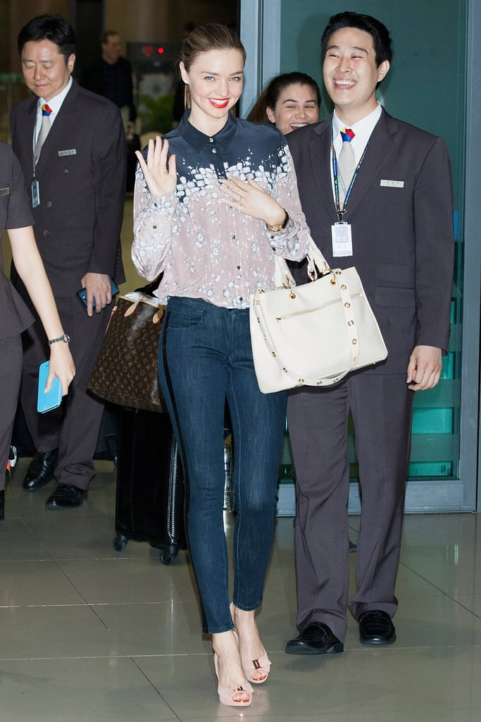 Miranda Kerr arrived in South Korea looking polished in a printed silk button-down, skinny denim, an off-white bag, and nude peep-toe pumps.