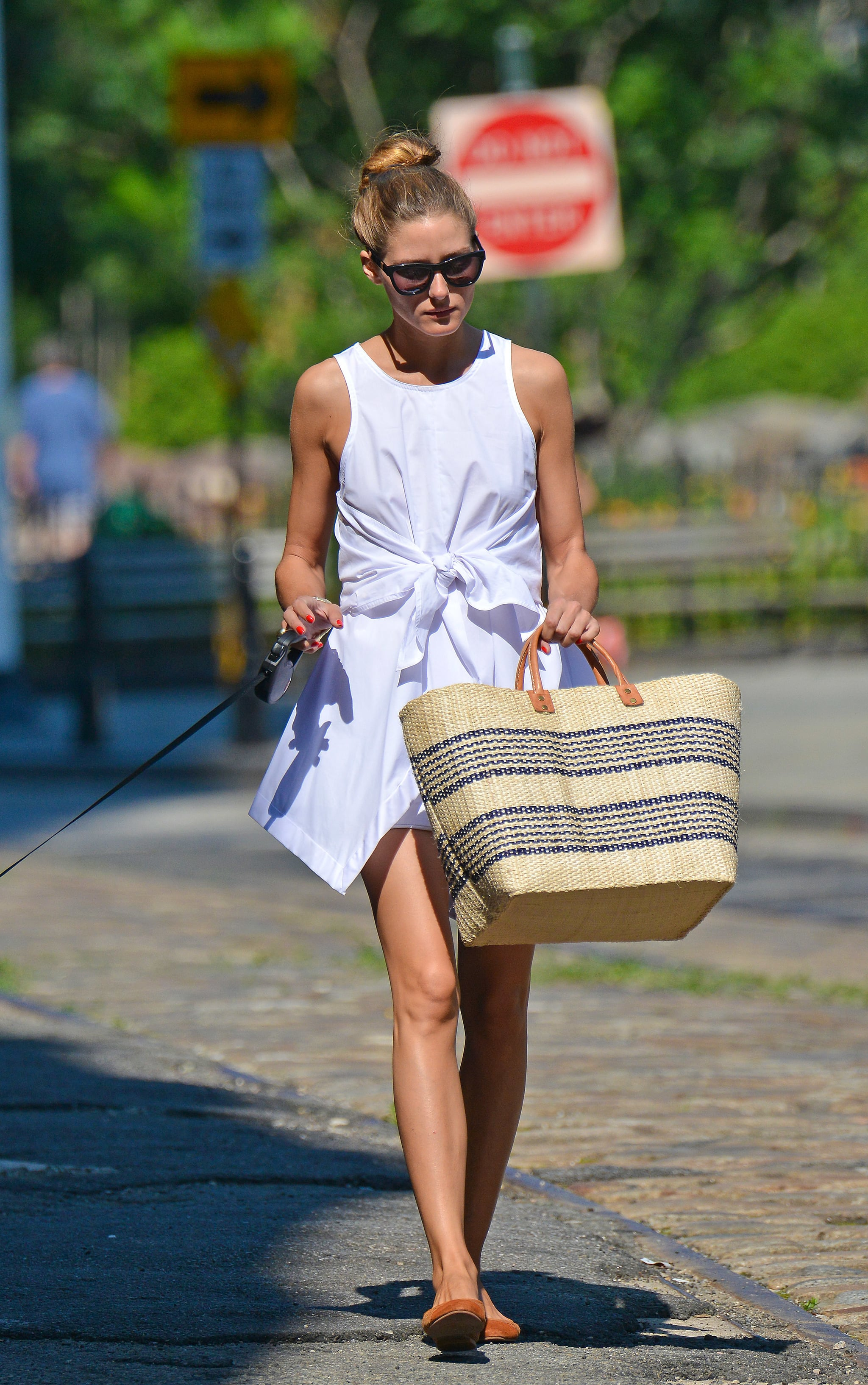 By day, Olivia accessorized her LWD with a straw tote and flats.