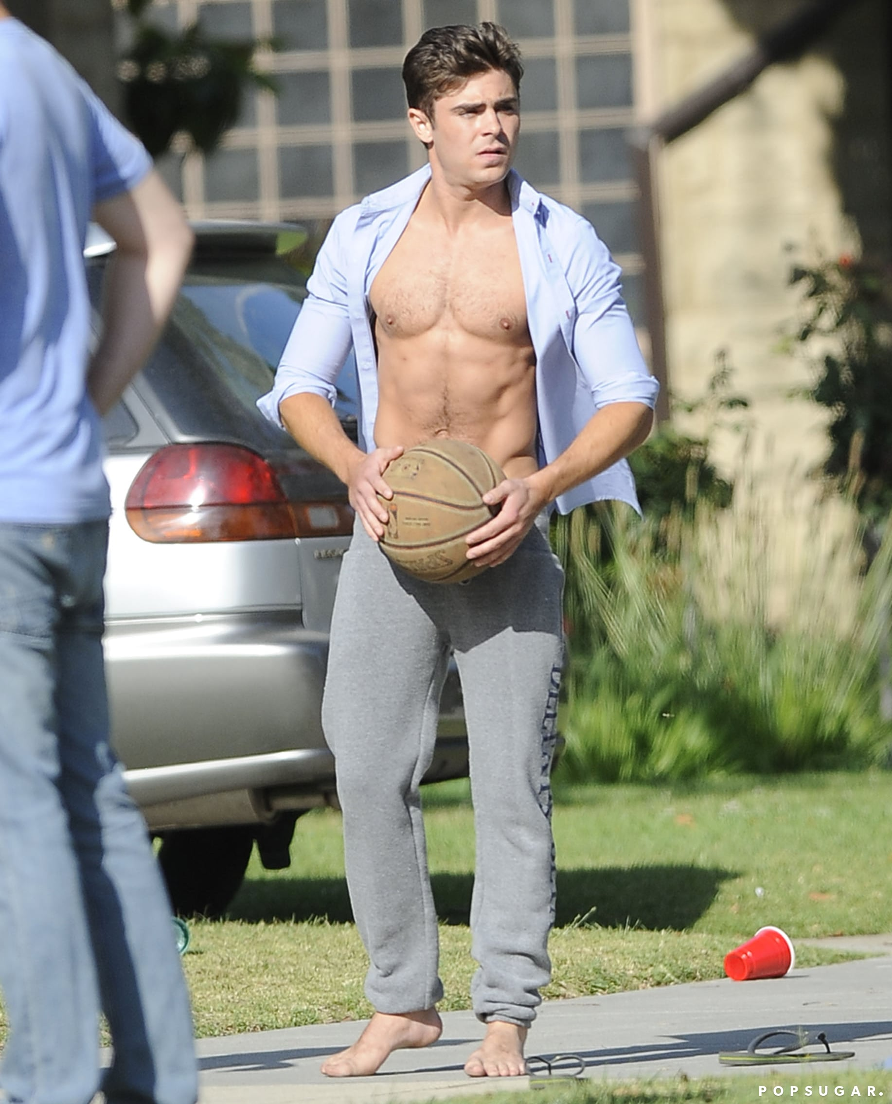 Zac Efron let his shirt fly loose while filming Neighbors in LA in May.