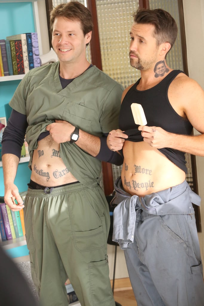 Morgan (Ike Barinholtz) and guest star Rob McElhenney, who plays his cousin Lou, show off their stomach ink.