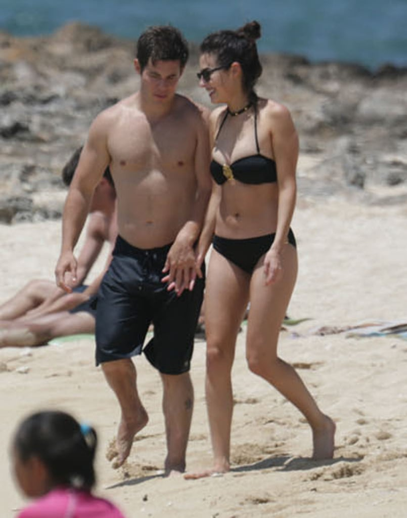 Adam DeVine and his girlfriend, actress Chloe Bridges, held hands as they walked along a beach in Oahu, Hawaii, in May 2015.