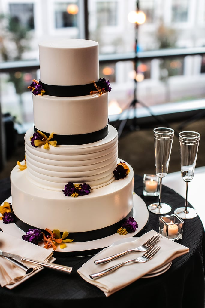 Black ribbon and a few bright flowers pop against the white frosting on this modern stunner.
