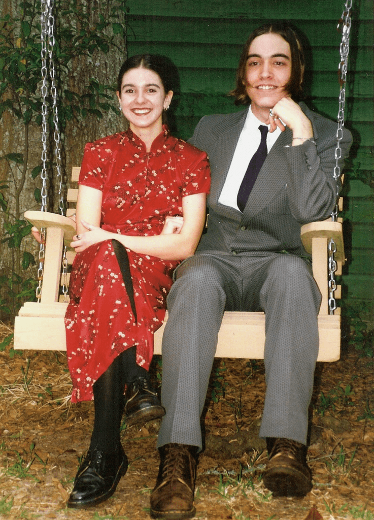 """""""My date and I both wore Doc Martens (hey, it was the '90s!). We didn't get our photo taken at the prom, just beforehand in my friend's backyard. I bought the dress the day before at the mall, and I called my date the day of the prom to ask him out. Luckily, he had a vintage suit to wear. We ended up dating for the rest of high school. My mom fixed my hair with fresh red flowers in a bun."""" — Nancy Einhart"""