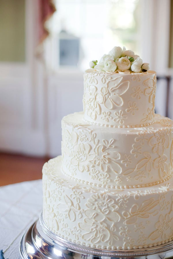 An easy recipe for an elegant cake that's hard to forget? A floral and lace-like pattern that's topped off with white roses.  Photo by Corbin Gurkin Photography via Style Me Pretty