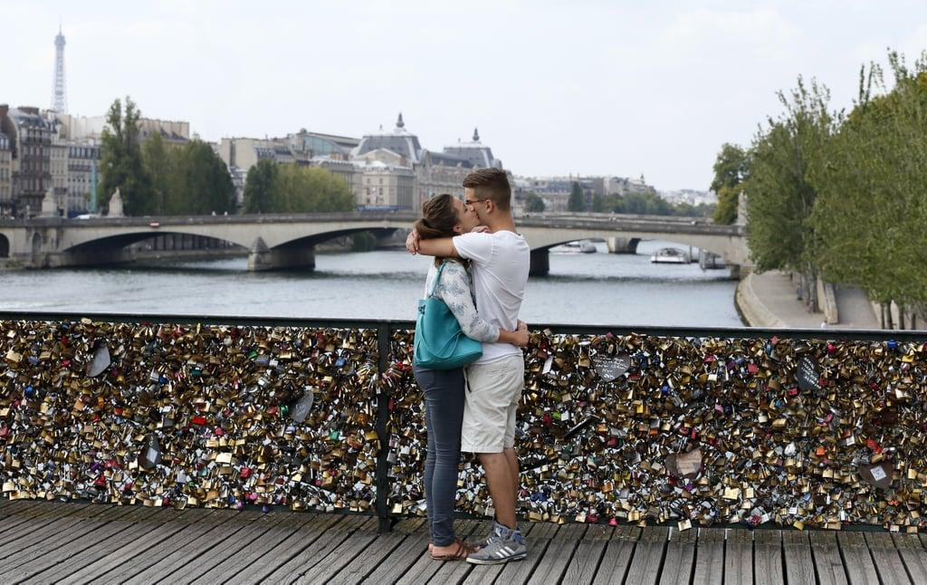 A pair of lovebirds kissed in Paris alongside love padlocks on the Pont des Arts bridge.
