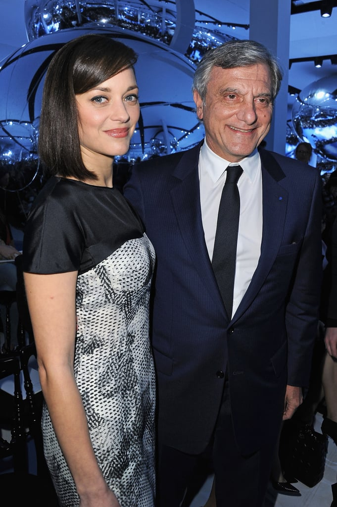 Under her sleek outerwear, Marion Cotillard worked a printed black and white sheath while posing with Christian Dior's CEO, Sidney Toledano.