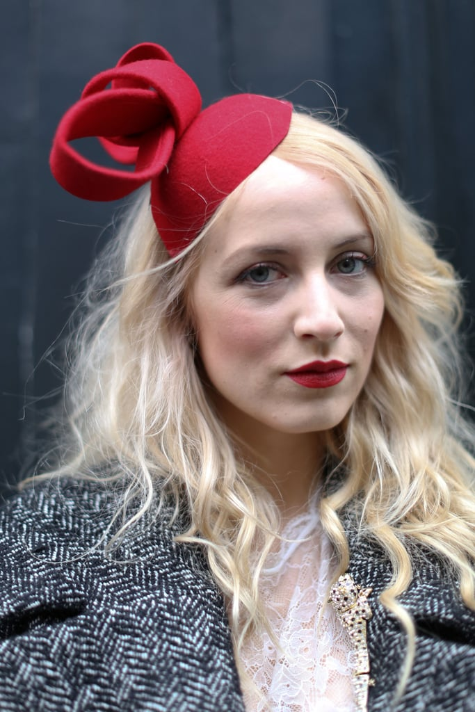 A quirky fascinator lent infinite personality and echoed the red hue on her lips.