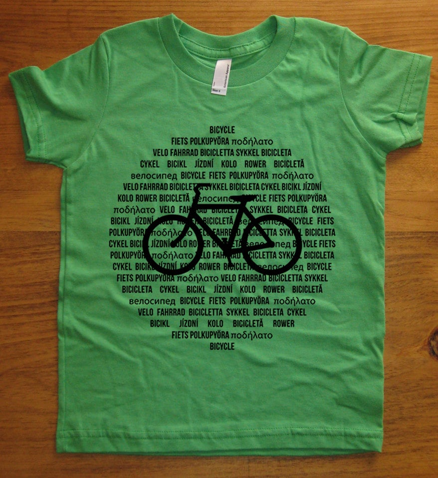 """This unique kids' bicycle shirt ($16), available in seven colors, highlights the word """"bicycle"""" in 18 languages."""