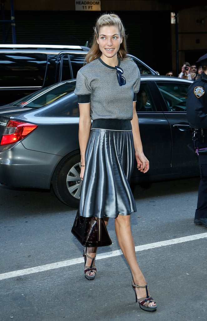 Jessica Hart paired a sporty short-sleeved sweatshirt with a metallic pleated skirt, a Louis Vuitton bag, and t-strap Yves Saint Laurent sandals en route to Calvin Klein.