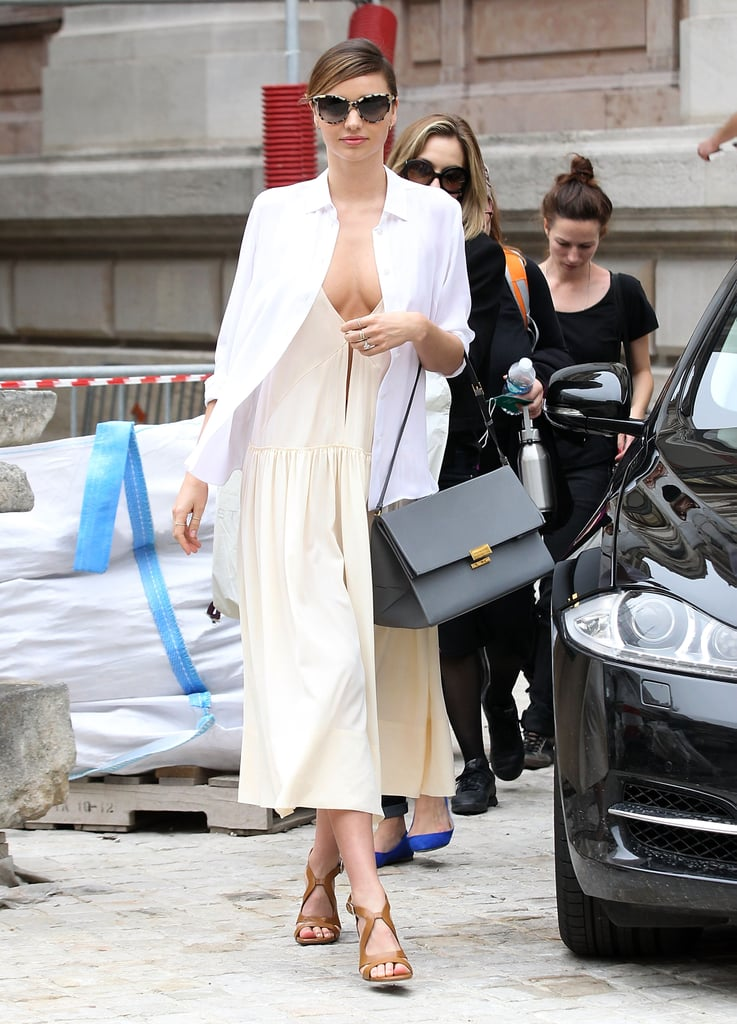 Miranda Kerr topped her plunging midi dress with a crisp white blouse outside the shows at Paris Fashion Week. She completed her billowy style with a gray bag and tan sandals.