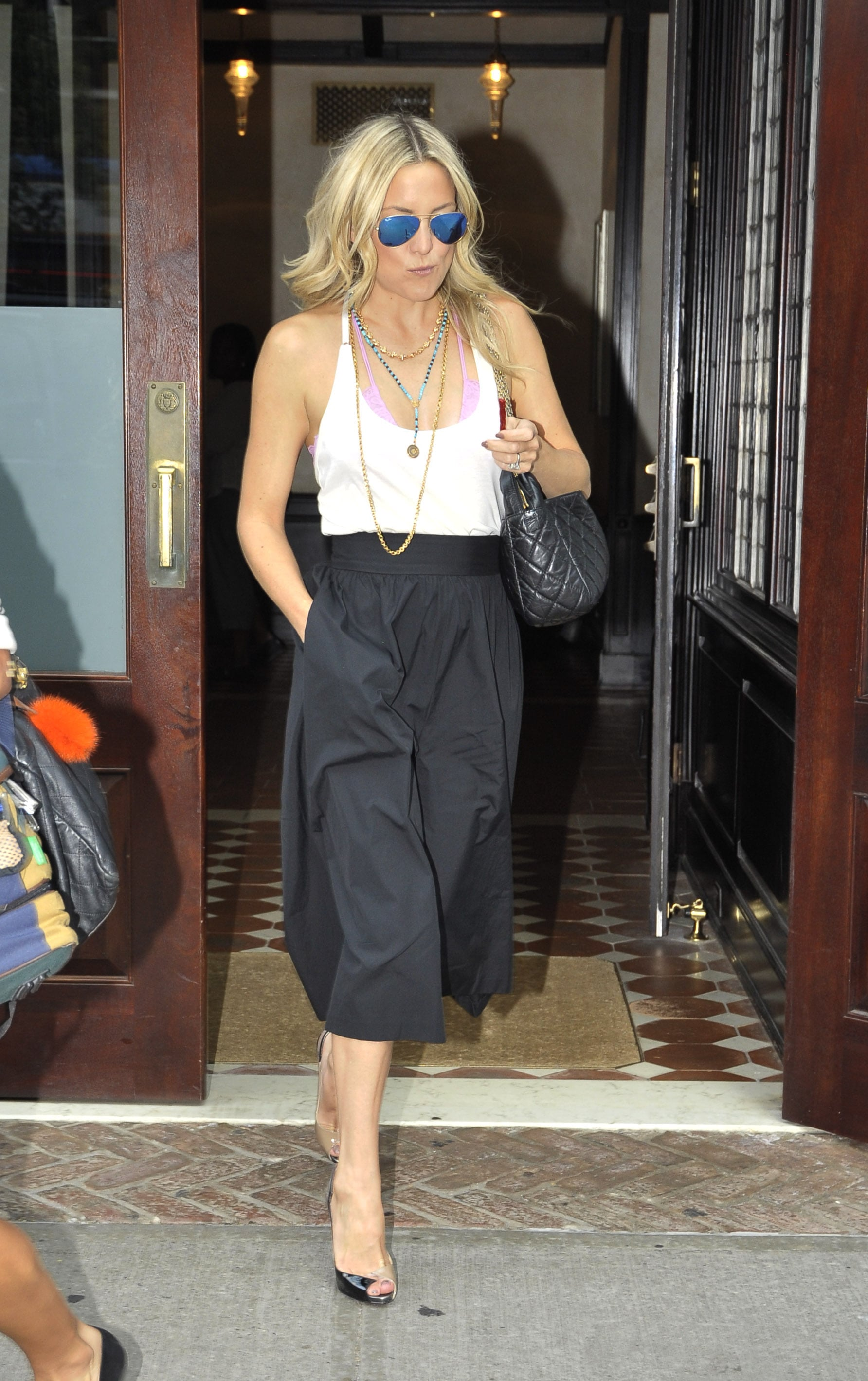 Kate chose to pair her trousers with a low-cut tank, so as to let her sugar-pink bralette straps peek out. By layering a couple of beaded necklaces on top and slipping on her blue-mirrored Ray-Ban aviators, she brought her colorful personality to light. See how you can roll like Kate below. The look is totally obtainable —as for those flawlessly tousled beach waves, that's all Kate.