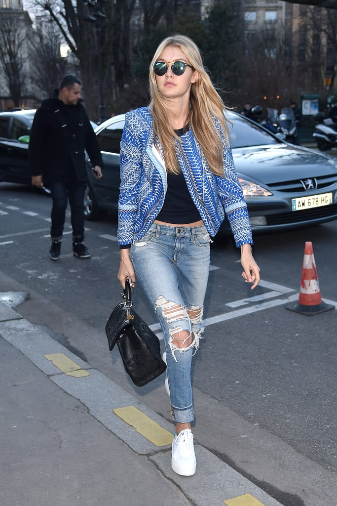 For a casual cool-girl look, Gigi Hadid paired her ripped light-wash denim with white sneakers, a black tank, and a blue printed jacket.