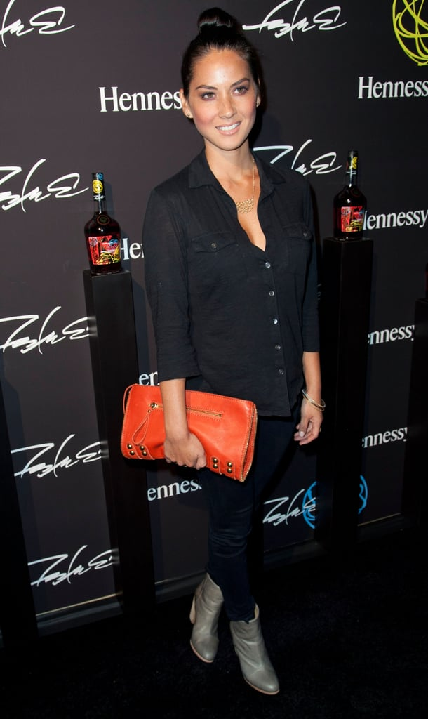 Olivia Munn dressed up a casual all-black look with a pop of orange on her oversize clutch — plus the bag's cool-girl studded detail.