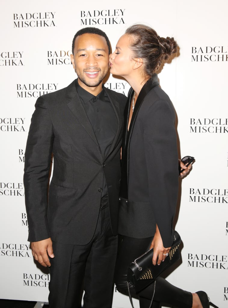 Chrissy Teigen planted a kiss on her fiancé, John Legend, at the Badgley Mischka show on Tuesday.