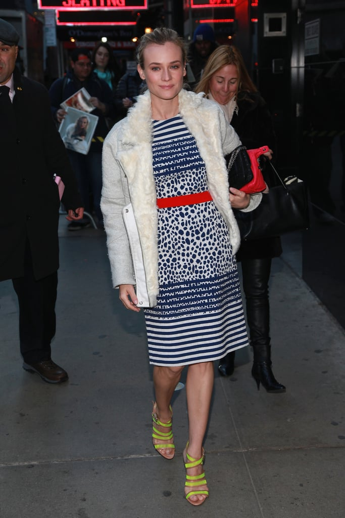 For her Good Morning America appearance in NYC, Diane Kruger layered up in a printed Preen dress with a cozy white coat and neon yellow Loeffler Randall sandals.