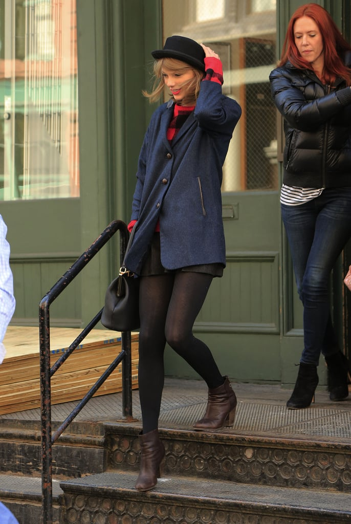 On Wednesday, Taylor Swift held onto her hat during a windy day in NYC.