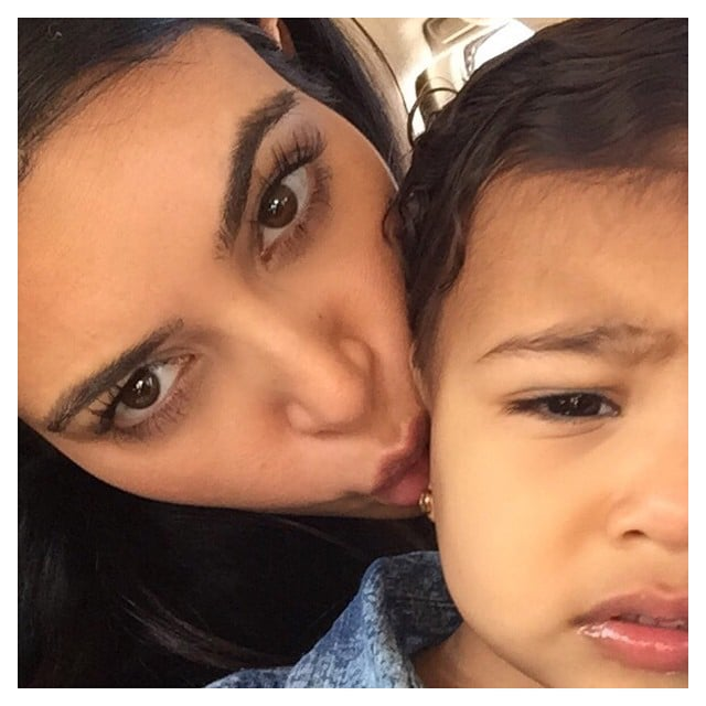 """""""I don't know if she's annoyed with my million daily kisses or my alien face,"""" Kim wrote about this cute picture."""