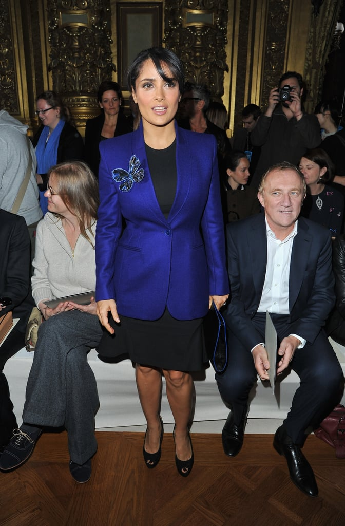 Salma Hayek dresses up her form-fitted black sheath with a cobalt blue blazer — complete with butterfly brooch — at the Stella McCartney show.