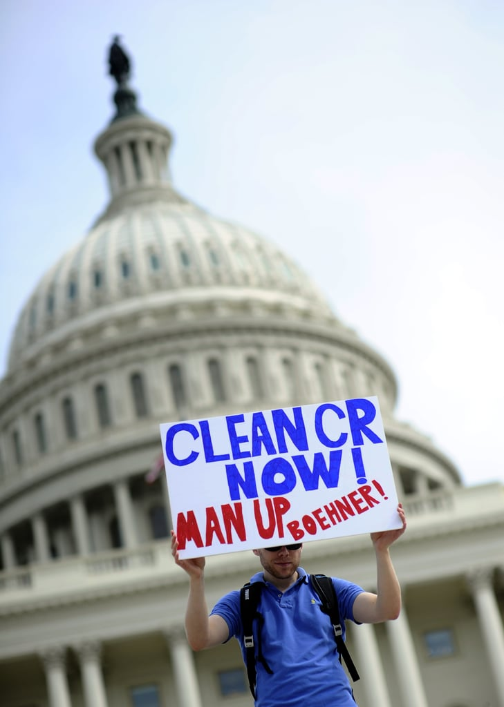 """A person at the DC demonstration held up a sign that read, """"Clean CR now! Man up, Boehner!"""""""