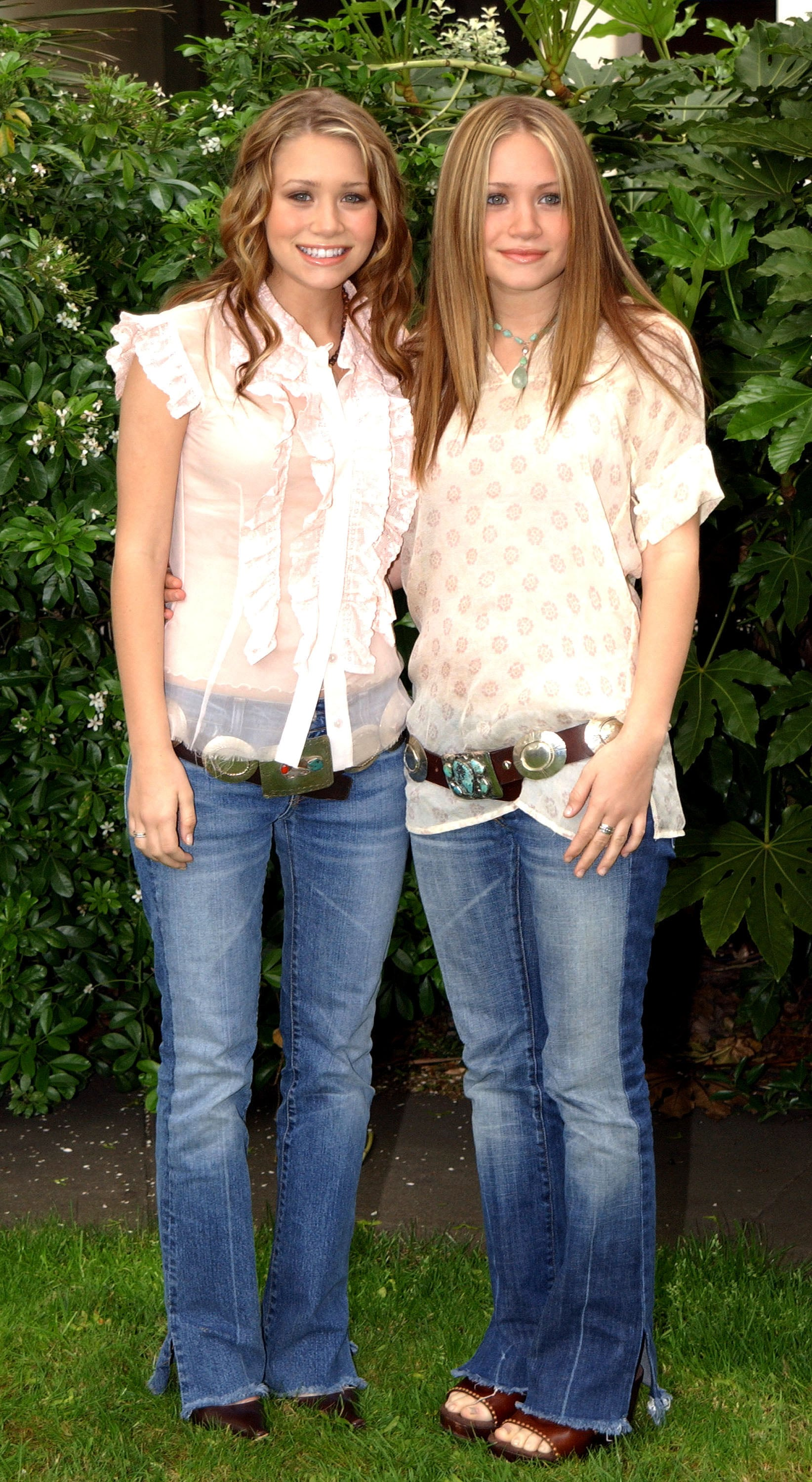 Twinning combo: Mary-Kate and Ashley styled washed denim with oversize cowboy belts and gauzy tops during a 2005 charity photocall in London.  Ashley chose a ruffle-detail blouse and pointed pumps. Mary-Kate went full-on boho-chic in a printed tunic and leather clogs.