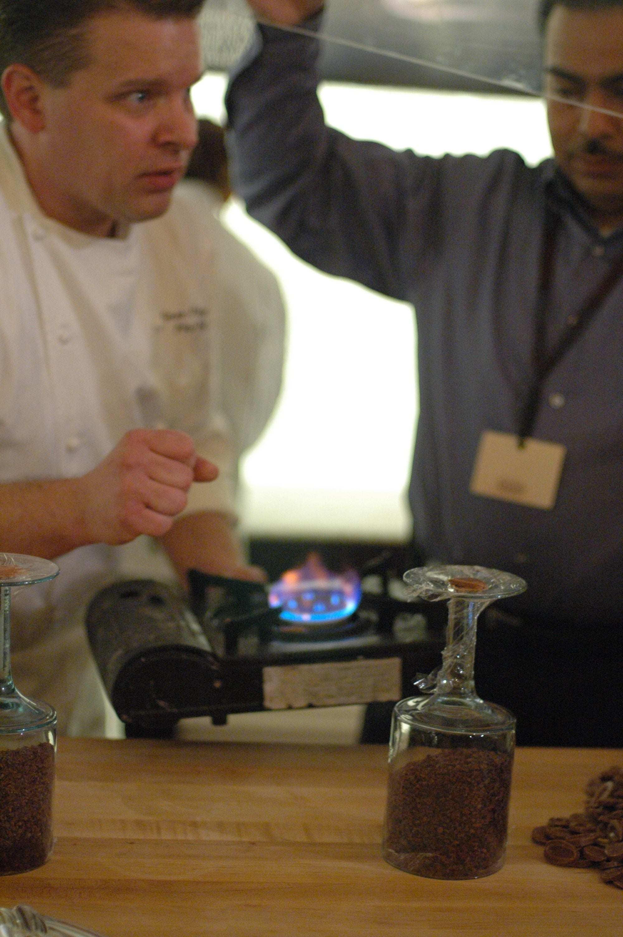 """George Fritzche heats chocolate to create a """"glue"""" for his display."""