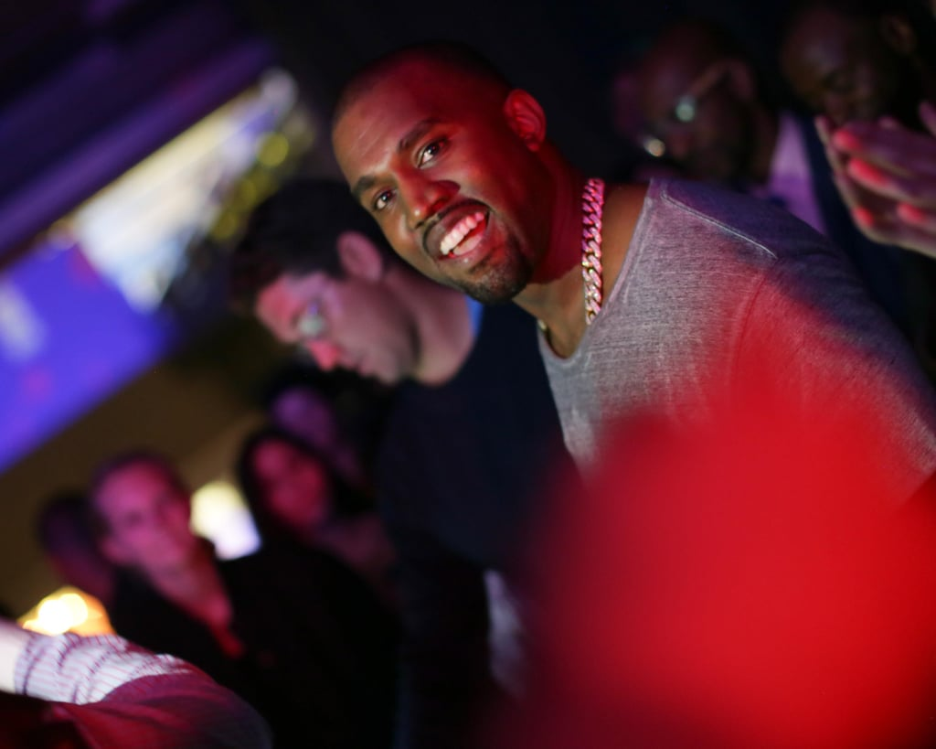 Kanye West smiled while presenting his songs to his friends.