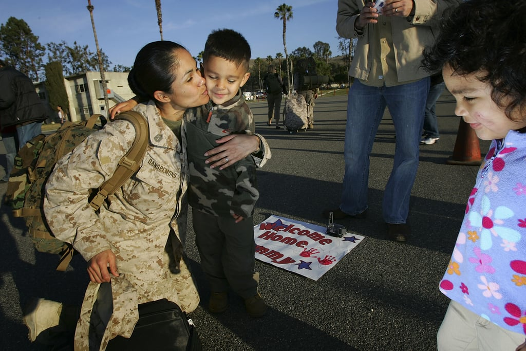 At a 2006 homecoming ceremony, Gunnery Sgt. Deborah Dangremond kisses her son, Tyler, 4, as her daughter, Basia, 3, watches with a smile.