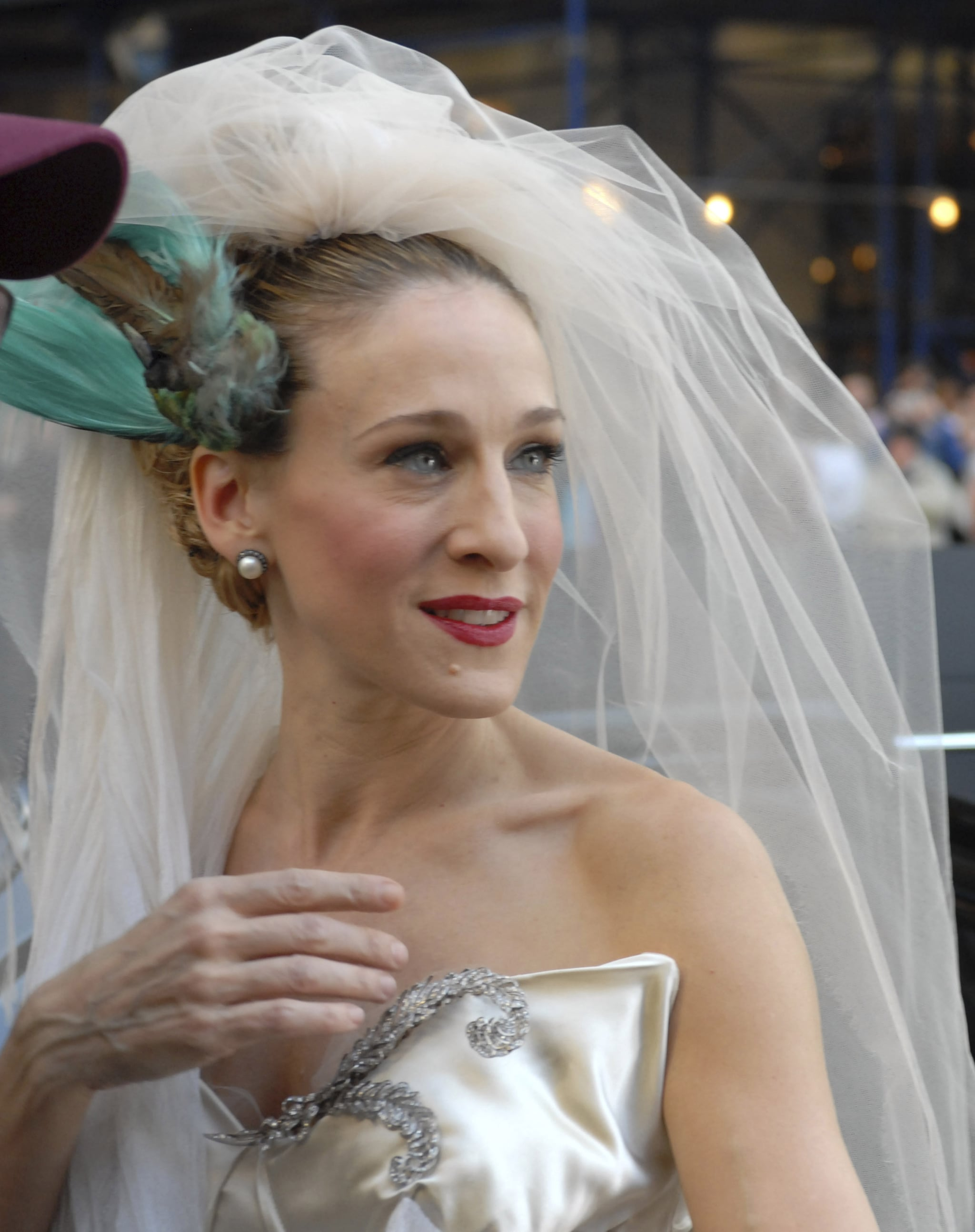 """""""I put a bird on my head!"""" Carrie goes for a sophisticated and sleek bridal beauty look with a slick updo and a pop of red on her lips."""