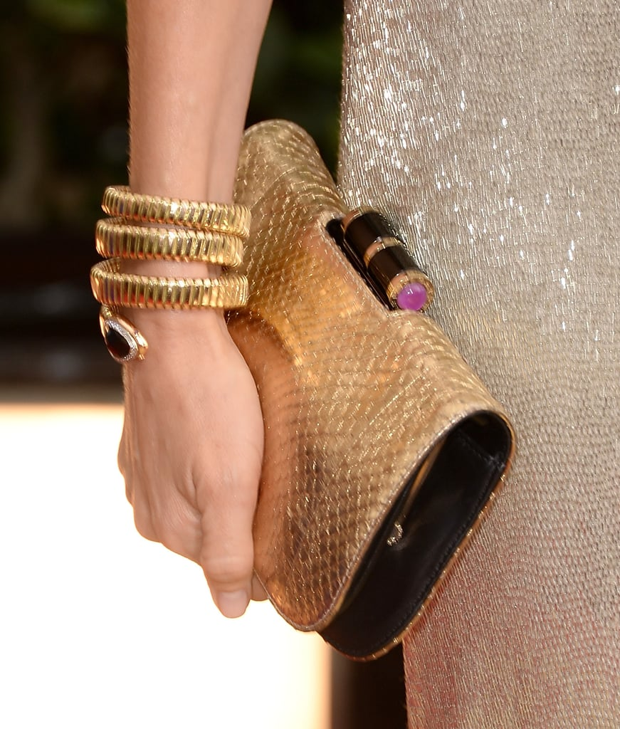 Naomi Watts added interest with an exotic Bulgari yellow gold serpenti double coil bracelet and a coordinating gold clutch.