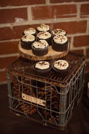 In this case, the cupcakes themselves are downplayed, and it's all about the presentation — a crate filled with pine cones and a slice of wood for a pedestal are rural and rustic. Photo by Studio222 Photography via Source