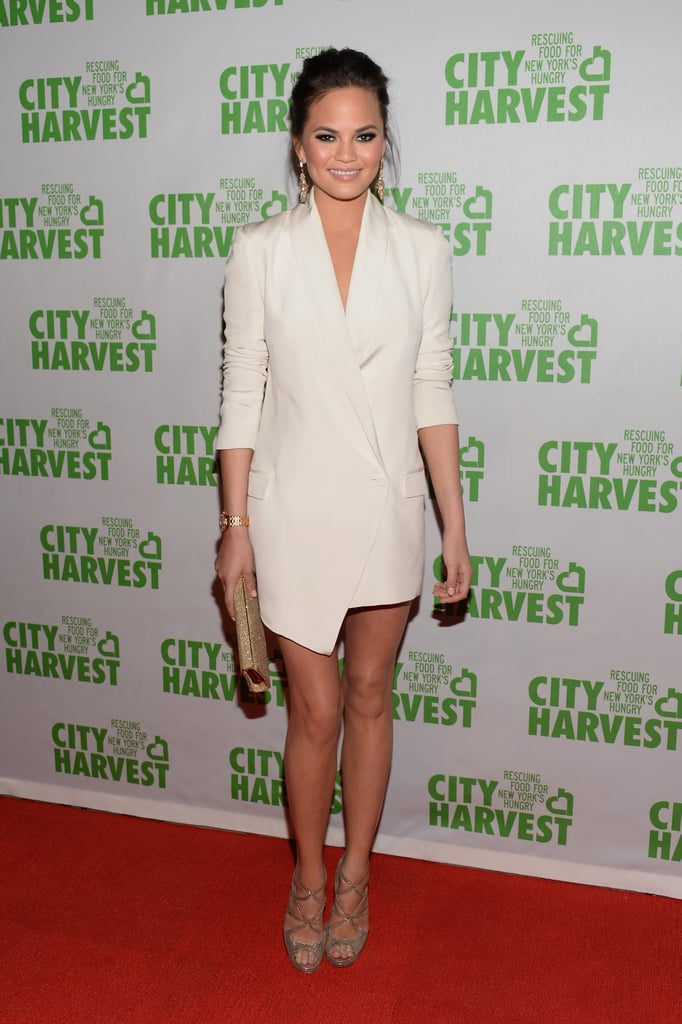 Chrissy Teigen took the sexy menswear approach in a white tuxedo dress at an event in NYC. She pulled in a dose of shine with a gold glitter clutch, matching strappy sandals, and gold drop earrings.