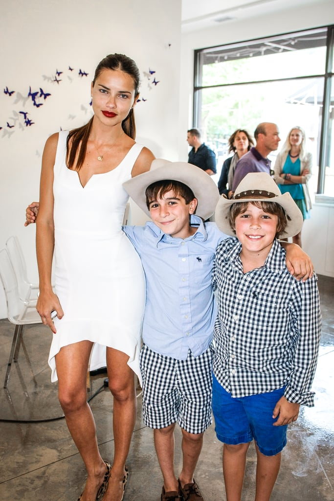 Adriana Lima looked sexy and fresh in a high-low white dress at an exhibition opening in Aspen.
