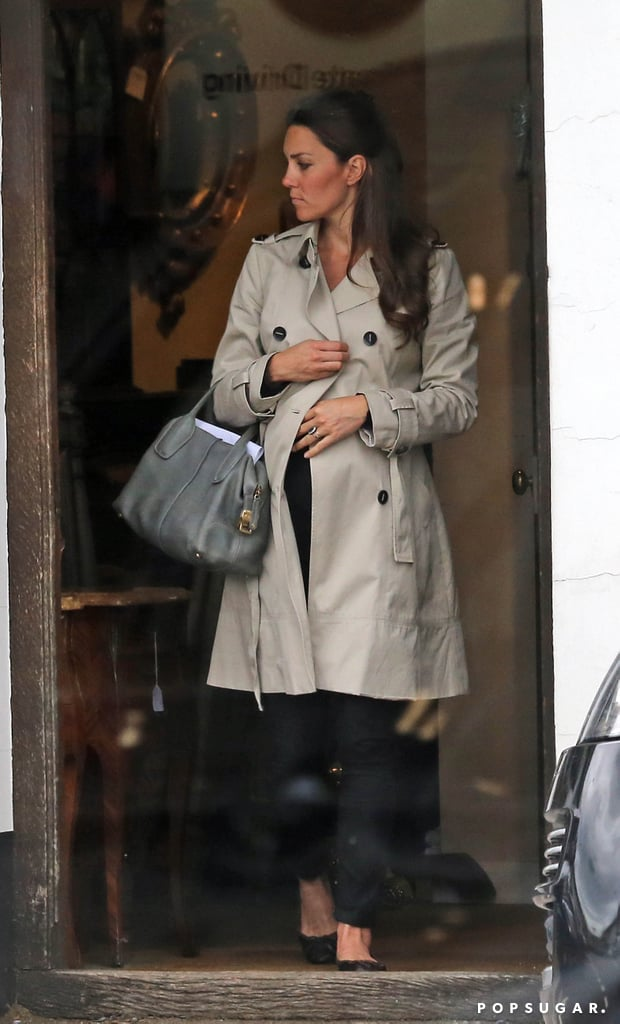 Kate Middleton wore a black outfit and a trench coat.