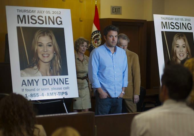 """Nick poses in front of the """"Missing"""" posters."""