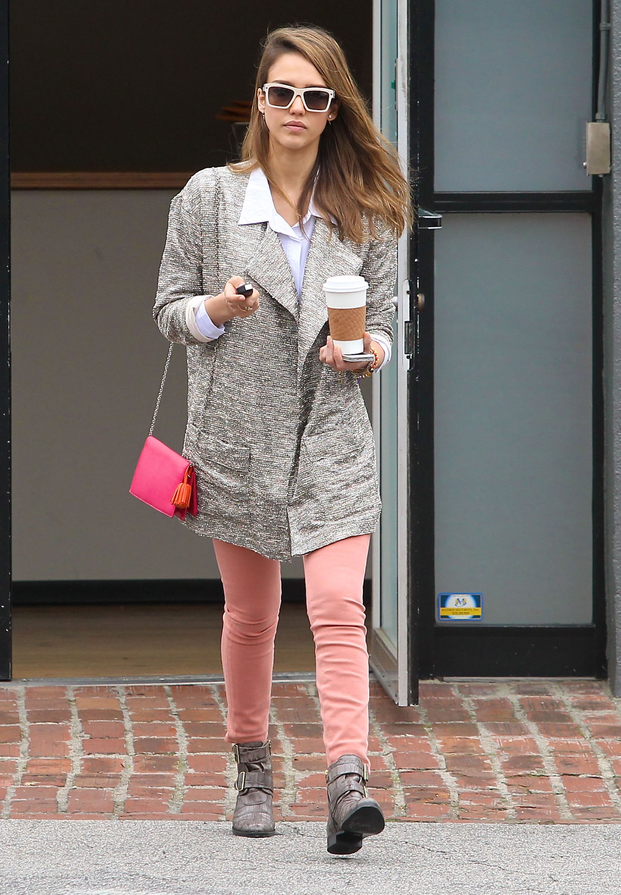 Jessica Alba played with proportions, donning a metallic Joe's Jeans jacket, peach skinny jeans, and a crisp white button-down in LA. She jazzed up her neutral pairing with snakeskin moto boots, a fuchsia Loewe crossbody, and retro shades.
