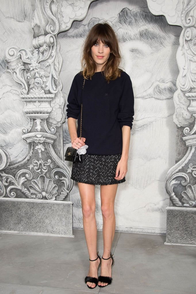 Alexa Chung posed outside Chanel, showing off her usual boy-meets-girl fashion sense in a slouchy knit, tweed mini skirt, and ankle-strap heels.