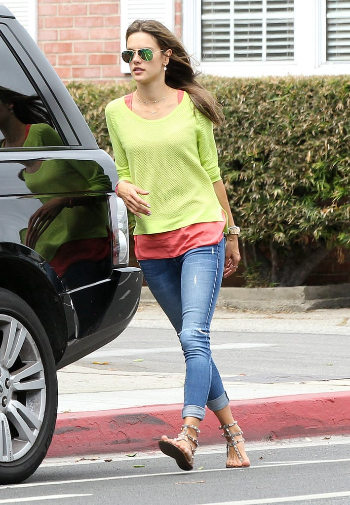 Alessandra layered a neon yellow sweater over an orange tank, then completed her LA style with cuffed Black Orchid skinny jeans, embellished sandals, and mirrored aviator sunglasses.